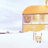 アイスランドの雪景色の中の黄色いテラス様式の建物と黄色いショッピングカート