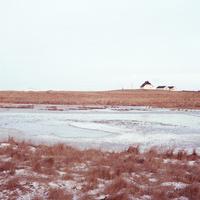 アイスランドの冬の草原の中の凍った池とその向こうに見える小さな建物