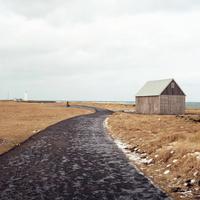 アイスランドの海岸へ続く草原の中にある凍った道と魚を干すための小屋