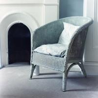 イギリスの部屋の中の白い絨毯と白いラタンの椅子とその向こうに見える白い暖炉