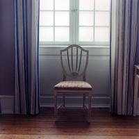 ストライプのカーテンがかかり逆光が差す窓の前の古い様式の椅子