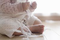 室内でティッシュをちぎって散らかす赤ちゃんの手 10770000179  写真素材・ストックフォト・画像・イラスト素材 アマナイメージズ