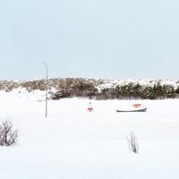 アイスランドの雪が積もった平地に遊具として置かれた船とタイヤで作られたブランコ