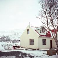 アイスランドの南部ラウガーバットンで積もった雪の山々を望む古い農家の家と木