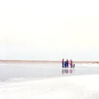 アイスランドの凍った湖の上でスケートなどをする人々がぼんやり見える風景