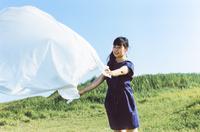 草原で白いシートを広げる女性