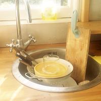 イギリスの窓辺の光り輝く木目のキッチンのシンクに置かれた洗う前の食器類