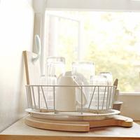 イギリスのキッチンの食器ラックに置かれたグラスやカップが窓辺からの光に透けている情景
