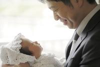 新生児を抱いてみつめあう父親