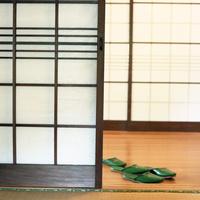 ガラス戸とスリッパと奥に障子の戸が見える廊下
