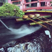 赤い橋の手前の手水舎と柄杓