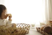 朝の食卓でパンを食べる赤ちゃん