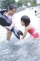 サメの浮き輪を持って水遊びをする水着姿の姉妹