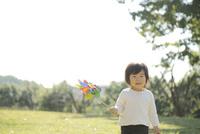 風車を持って草原に立つ幼児