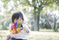 座って風車をいじる幼児 10770000719  写真素材・ストックフォト・画像・イラスト素材 アマナイメージズ