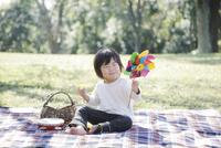 レジャーシートに座って風車を眺める幼児 10770000720  写真素材・ストックフォト・画像・イラスト素材 アマナイメージズ