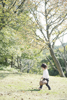 かごを持って芝生を歩く幼児