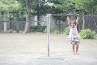 鉄棒にぶら下がって微笑む少女