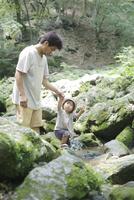 沢を歩く父親と幼児