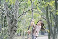 笑顔で木登りする少女