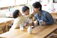 キッチンのテーブルでおやつを食べる兄弟と母親