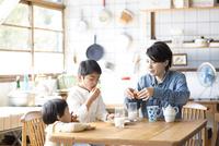 キッチンのテーブルでドーナツを食べる兄弟と母親