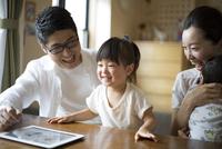リビングでタブレットを使う家族 10778001286| 写真素材・ストックフォト・画像・イラスト素材|アマナイメージズ