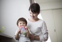 母親の膝の上に座りマグカップでミルクを飲む赤ちゃん
