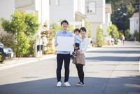 家の前の路上で白ボードを持つ夫と赤ちゃんを抱いて微笑む妻