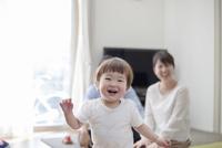 リビングで歩く赤ちゃんとそれを見守る父親と母親