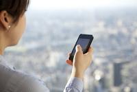 高層ビルの窓際でスマートフォンを使っている女性