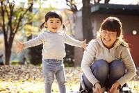 秋の公園で一緒に遊んでいる親子 10798000264| 写真素材・ストックフォト・画像・イラスト素材|アマナイメージズ