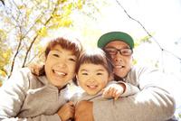 秋の公園でカメラをのぞきこむ3人家族 10798000271| 写真素材・ストックフォト・画像・イラスト素材|アマナイメージズ