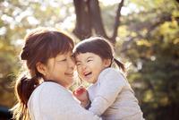 秋の公園で一緒に遊んでいる親子