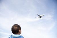 空を飛んでいる飛行機を眺めている子供 10798000344| 写真素材・ストックフォト・画像・イラスト素材|アマナイメージズ