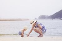 砂浜で遊んでいる母親と子供