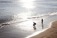 波打ち際で遊んでいる父親と子供をスマートフォンで撮影している母親