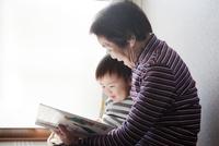孫に絵本の読み聞かせをしている祖母