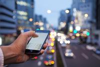 夕暮れの都会でスマートフォンを使うビジネスマンの手
