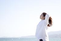 海岸でリラックスしている妊婦 10798000542| 写真素材・ストックフォト・画像・イラスト素材|アマナイメージズ