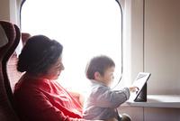 電車の中でタブレットpcを使っている母と子 10798000556| 写真素材・ストックフォト・画像・イラスト素材|アマナイメージズ
