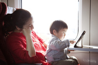 電車の中でタブレットpcを使っている母と子