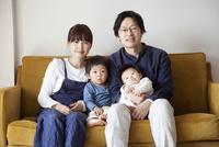 ソファーの上でリラックスする4人家族 10798000576| 写真素材・ストックフォト・画像・イラスト素材|アマナイメージズ