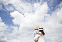 青空を背景に男の子を抱っこしている母親の後ろ姿