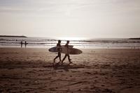 砂浜を歩いているサーファー2人組 10798000746| 写真素材・ストックフォト・画像・イラスト素材|アマナイメージズ