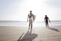 砂浜を海に向かって歩いているサーファー2人組