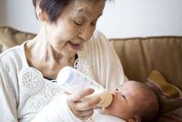 赤ちゃんに哺乳瓶でミルクをあげるおばあちゃん 10798000770| 写真素材・ストックフォト・画像・イラスト素材|アマナイメージズ