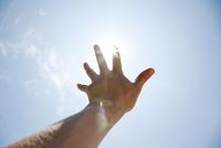 空に向かって手を伸ばす男性
