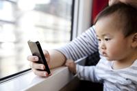 電車に乗って一緒にスマートフォンを見る母と子