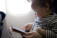 飛行機の機内でタブレットを見ている親子